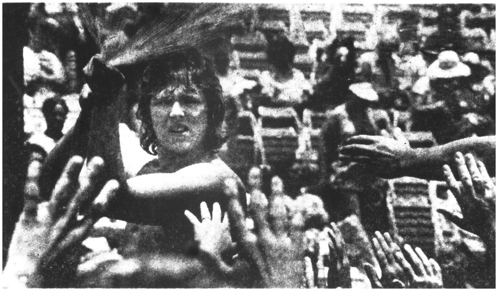 A concertgoer sprays water to help keep the crowd cool during the Rolling Stones' July 6, 1975, concert at the Cotton Bowl. More than 50,000 people attended the outdoor show despite triple-digit temperatures.