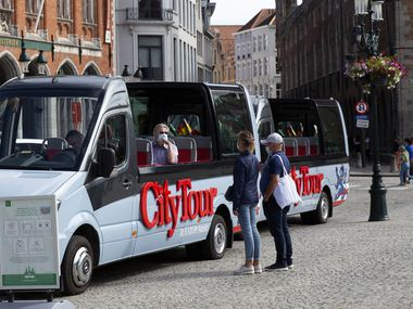 A tour operator in a protective face mask sits in an empty tour bus as he speaks with a couple on the market square of Bruges, Belgium.