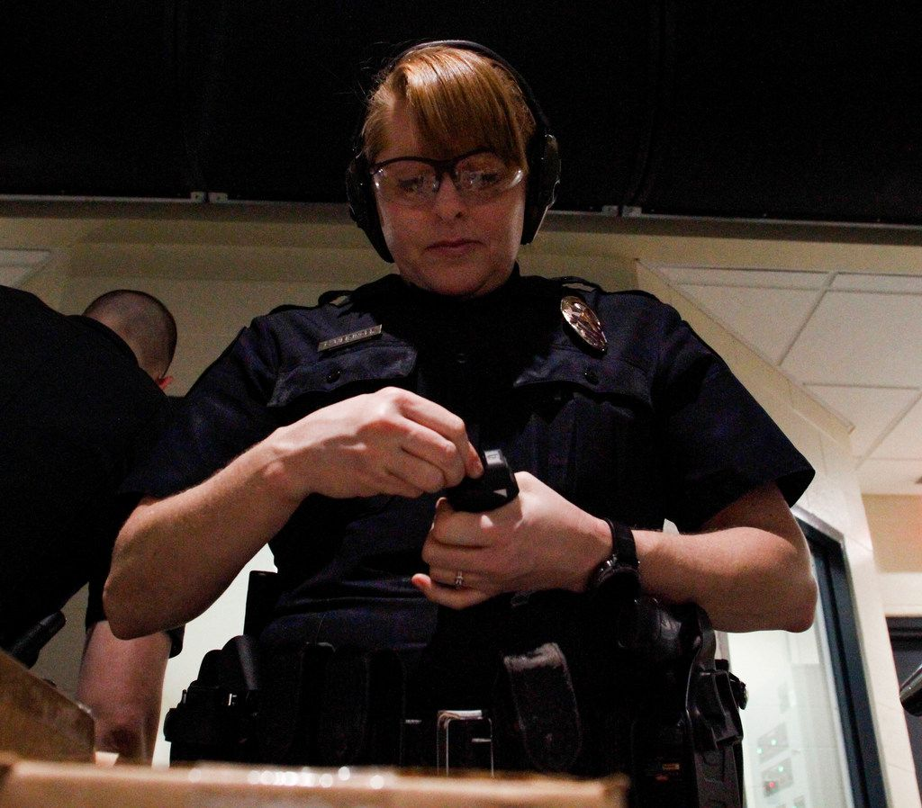 Christa Weisinger, a school resource officer with the Allen Police Department, loads her handgun as she prepares to go on the range.