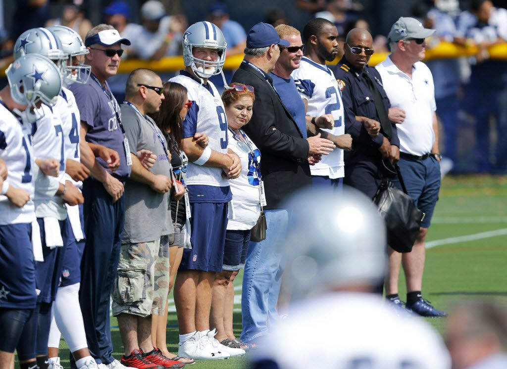 Dallas Cowboys quarterback Tony Romo (9) joined the family of slain officer Patrick Zamarripa, Dallas police Chief David Brown and Mayor Mike Rawlings who walked arm-in-arm onto the field for the opening day of training camp in Oxnard, California, Saturday, July 30, 2016. (Tom Fox/The Dallas Morning News)