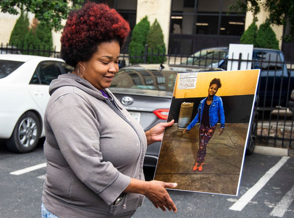 Shaquna Persley holds a picture of her daughter, Shavon Randle, outside  the Earle Cabell Federal Building in Dallas.
