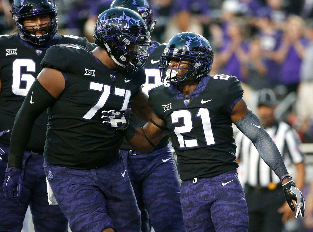 TCU's Lucas Niang (77) and running back Kyle Hicks (21) celebrate Hicks' touchdown during the first half of an NCAA college football game against Texas on Saturday, Nov. 4, 2017, in Fort Worth, Texas. (AP Photo/Ron Jenkins) ORG XMIT: TXRJ105