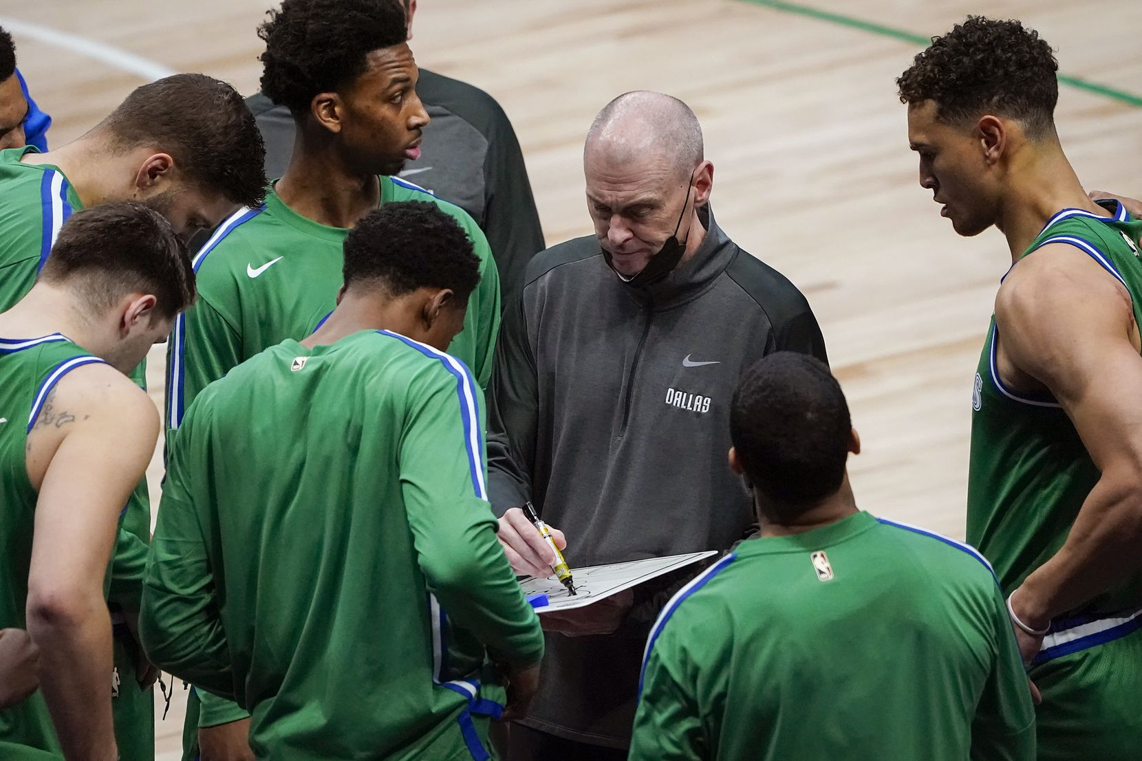 Mavericks head coach Rick Carlisle goes over plays with the team during the first half of a game against the Sacramento Kings.
