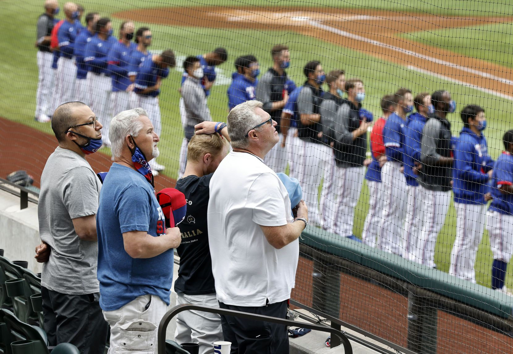 Texas Rangers fans and players stand for the national anthem before their game against the Milwaukee Brewers at Globe Life Field in Arlington, Texas. The teams were playing in an exhibition game, Tuesday, March 30, 2021.