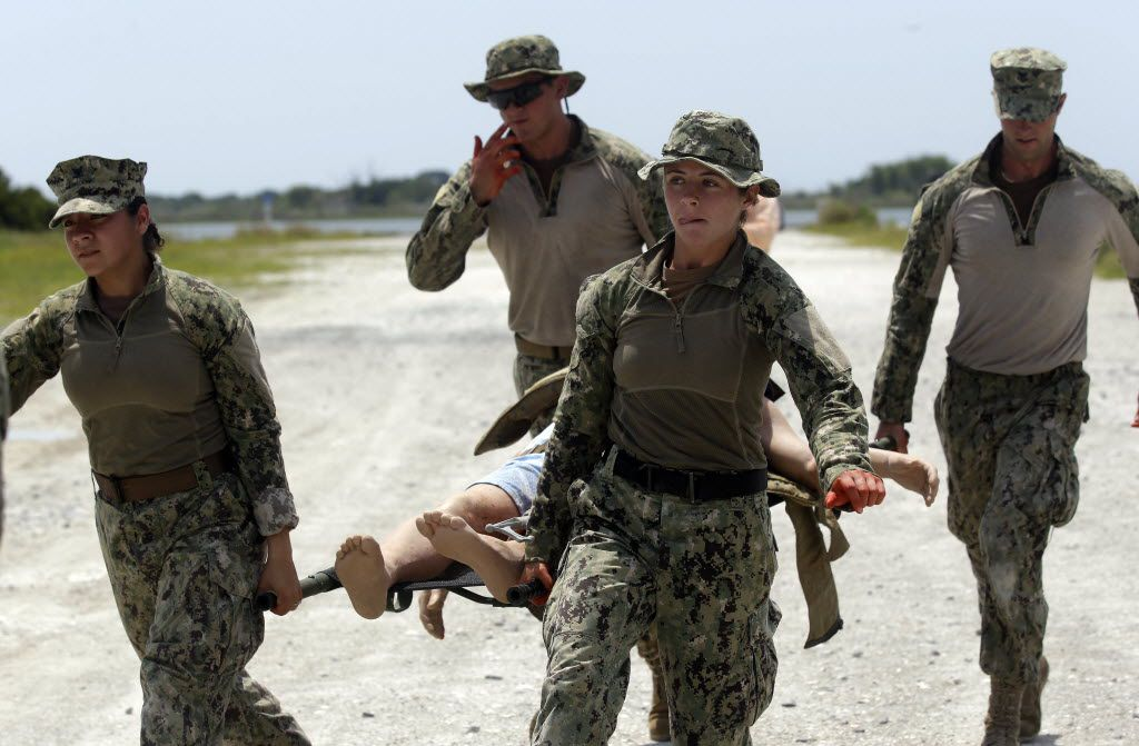 In this Aug. 13, 2013, photo, U.S. Navy Master-at-Arms Third Class Anna Schnatzmeyer (front left) and Master-at-Arms Third Class Danielle Hinchliff of Coastal Riverine Squadron 2 carry a mock wounded person as they participate in a U.S. Navy Riverine Crewman Course at the Center for Security Forces Learning Site at Camp Lejeune, N.C. They were among the first female participants have received this training as women begin to take on combat roles in the military.