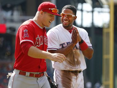 Texas Rangers shortstop Elvis Andrus (1) shares a laugh with Los Angeles Angels center fielder Mike Trout (27) between innings during the Los Angeles Angels vs. the Texas Rangers major league baseball game at Globe Life Park in Arlington on Saturday, October 3, 2015. (Louis DeLuca/The Dallas Morning News)