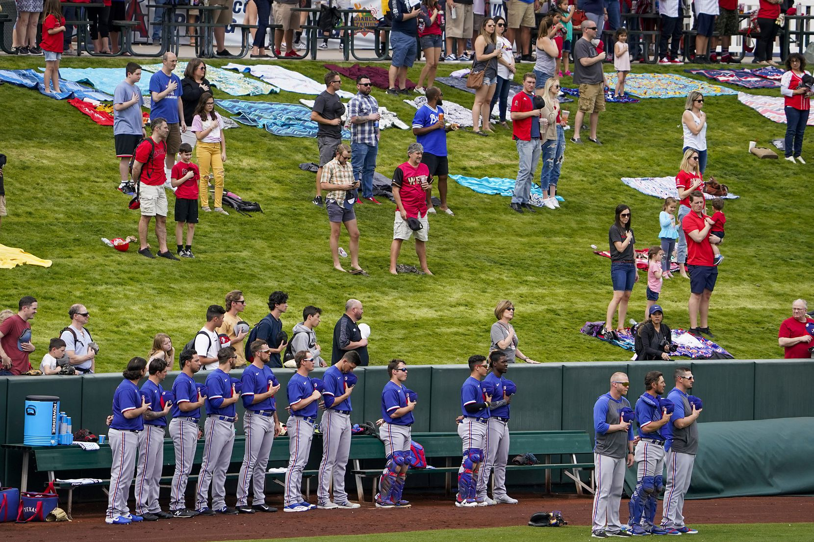 Fans stand along with the Texas Rangers bullpen for the national anthem before a spring training game against the Los Angeles Angels at Tempe Diablo Stadium on Friday, Feb. 28, 2020, in Tempe, Ariz.