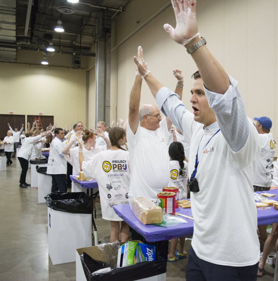 After Spreading Party announcer Trista Wyly called time at the end of the one hour Guinness World Record Spreading Party, Spread the Love volunteers stop making PB&J sandwiches and raise their hands.