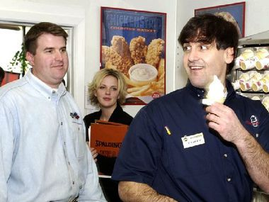 Dallas Mavericks owner Mark Cuban serves up a soft-serve cone to the approval of DQ Manager Parrish Chapman (left) during his stint behind the counter at the Coppell Dairy Queen off of Southwestern and Belt Line Roads.