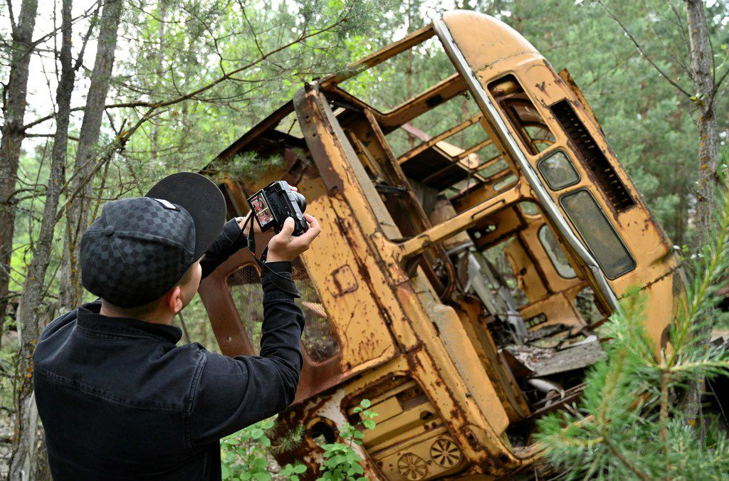 A visitor photographs the wreckage of a bus in the ghost city of Pripyat. The city was evacuated on April 27, 1986, a day after the Chernobyl nuclear disaster.