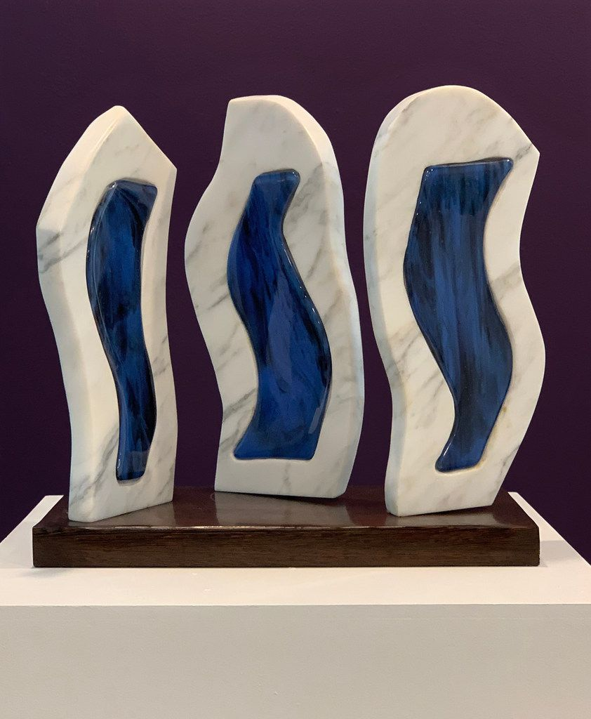 Adriana Cobo created Bailarines en Azul/Dancers in Blue, a 2019 white Italian marble and fused glass piece. At 83, she's the oldest artist in the exhibition.