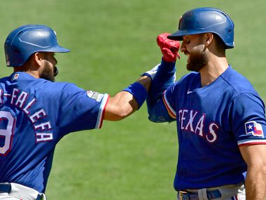 Isiah Kiner-Falefa (9) of the Rangers is congratulated by Joey Gallo (13) after hitting a solo home run in the first inning against the Angels at Angel Stadium of Anaheim on Sept. 21, 2020, in Anaheim, Calif.