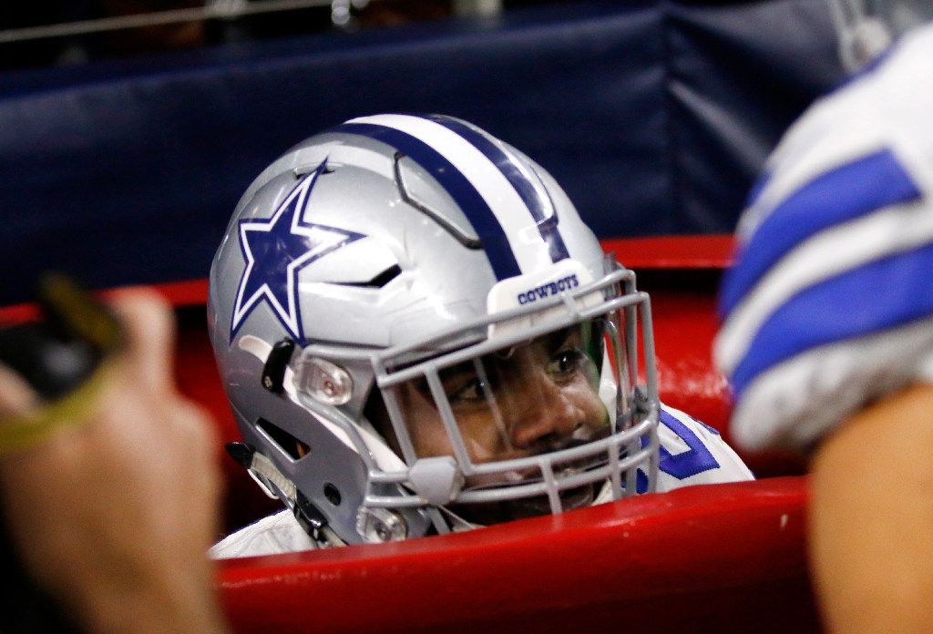 Dallas Cowboys running back Ezekiel Elliott peeks out of a large Salvation Army kettle after jumping into it celebrating a touchdown he scored on a running play in the first half of an NFL football game against the Tampa Bay Buccaneers on Sunday, Dec. 18, 2016, in Arlington, Texas. (AP Photo/Roger Steinman)