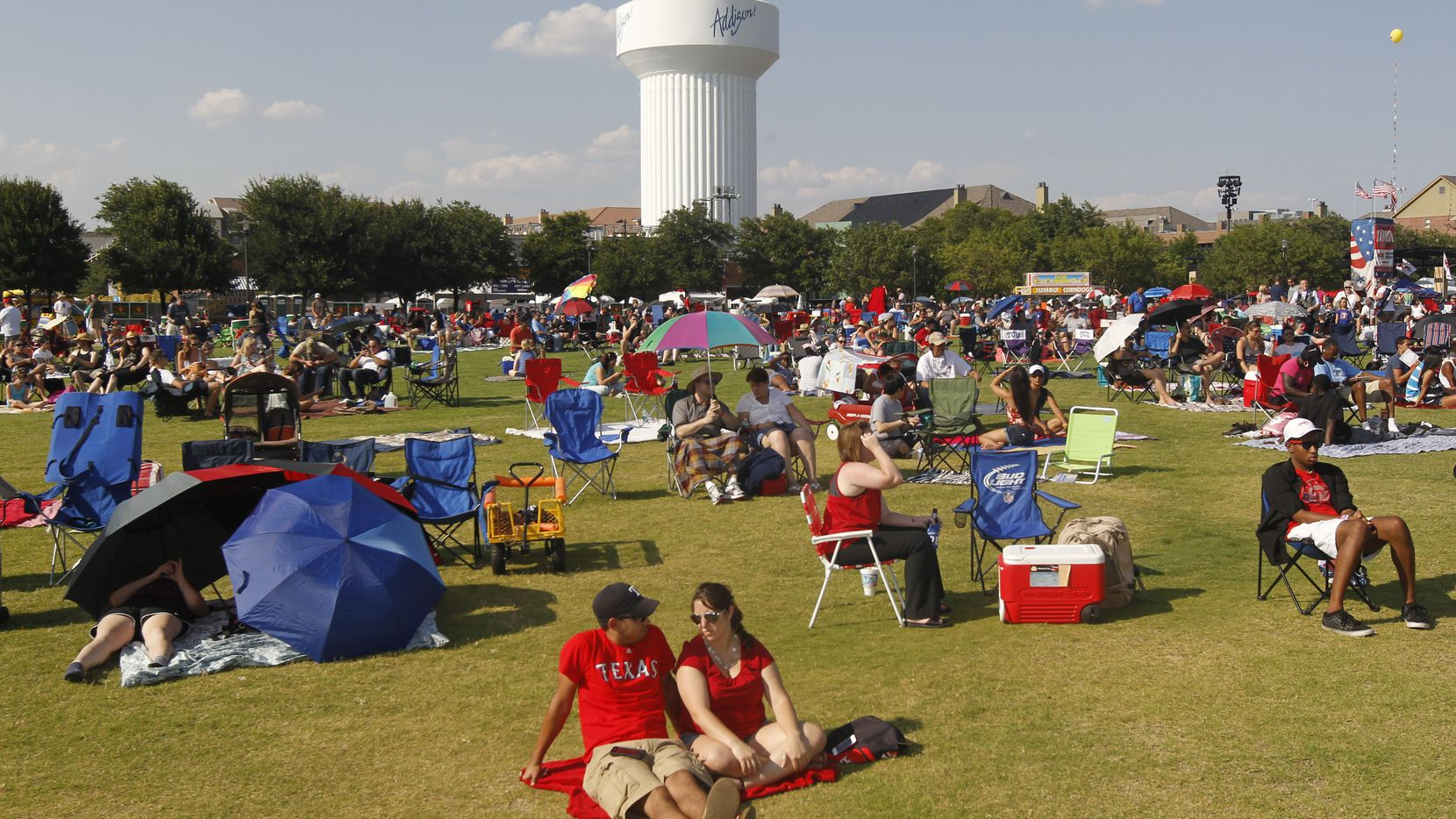 People prepare their viewing spots during the Kaboom Town Fourth of July celebration on Wednesday, July 3, 2013, at Addison Circle Park in Addison, Texas.  (AP Photo/The Dallas Morning News, Michael Ainsworth)