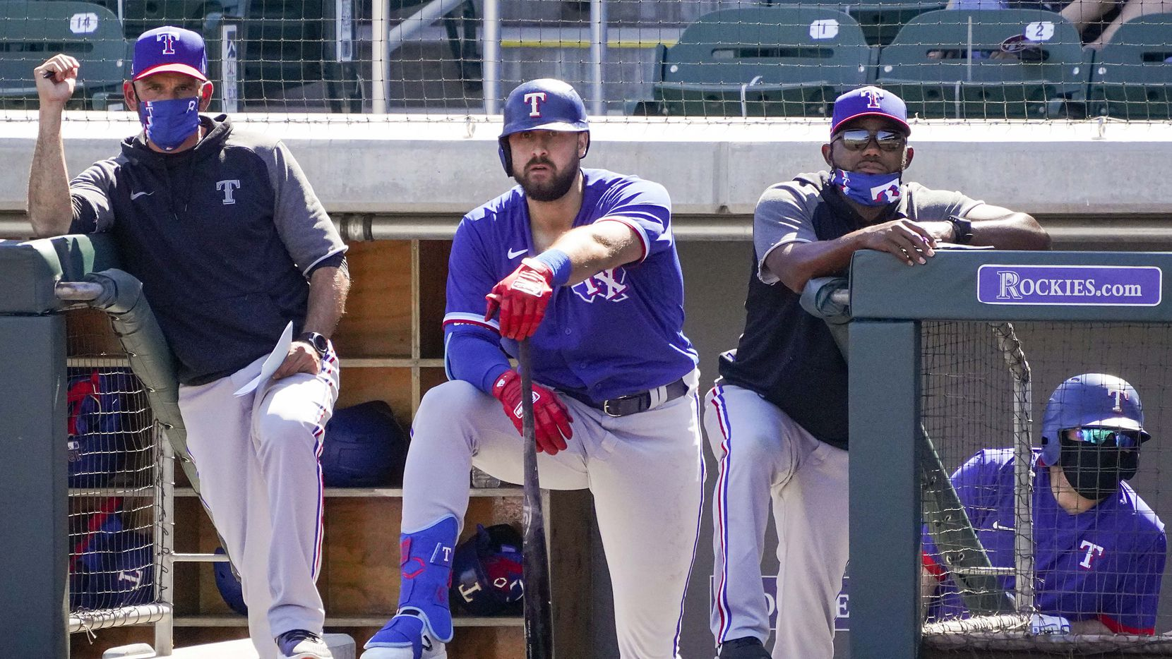 Texas Rangers manager Chris Woodward (left), outfielder Joey Gallo (center) and assistant hitting coach Callix Crabbe watch from the dugout during the third inning of a spring training game against the Arizona Diamondbacks at Salt River Fields at Talking Stick on Saturday, March 6, 2021, in Scottsdale, Ariz.