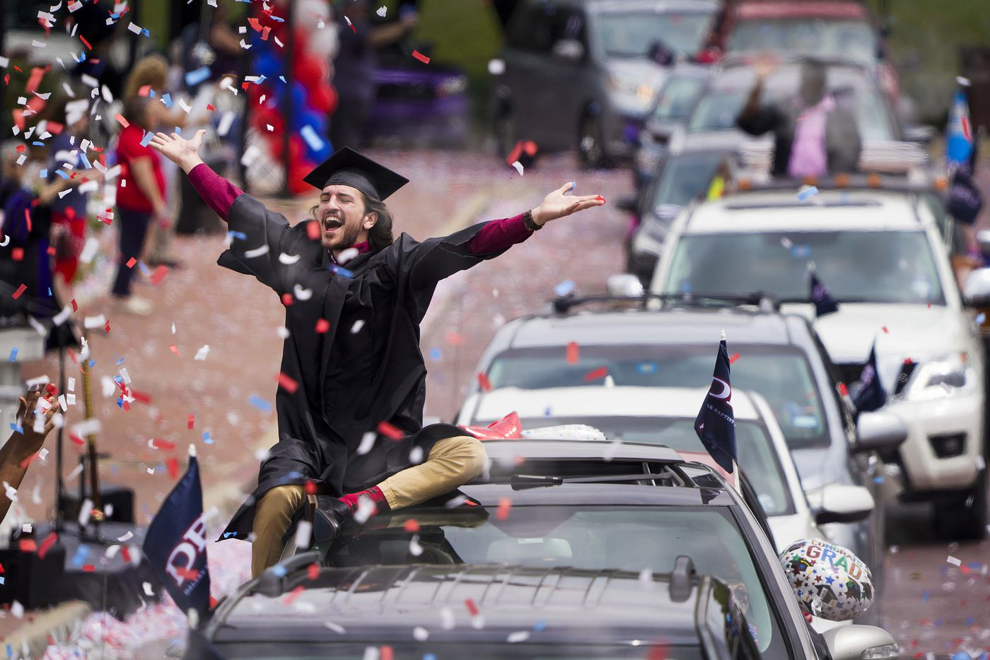 Graduate William Santini celebrates as confetti falls during a commencement car parade at Dallas Baptist University on Friday, May 15, 2020, in Dallas.  DBU graduates moved by car through the campus and had their names called as they passed Pilgrim Chapel before proceeding onward to collect their diplomas. Approximately 350 graduates passed through the campus in a parade of approximately 600 cars.