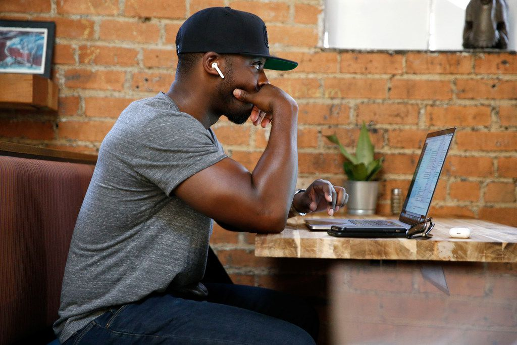 Collins Idehen, aka Colion Noir, works on his NRA TV show NOIR at a coffee shop in Deep Ellum.