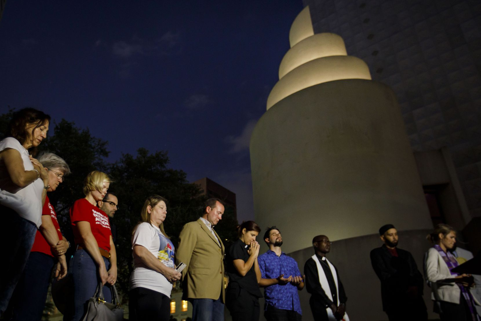 Activists, elected officials and faith leaders observe a moment of silence during a vigil at Thanks-Giving Square organized by Faith Forward Dallas in response to the mass shooting in Las Vegas on Monday, Oct. 2, 2017, in Dallas.