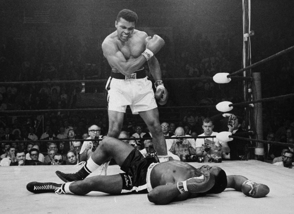 FILE - In this May 25, 1965, file photo, heavyweight champion Muhammad Ali stands over fallen challenger Sonny Liston, shouting and gesturing shortly after dropping Liston with a short hard right to the jaw in the first round of their title fight in Lewiston, Maine. The bout produced one of the strangest finishes in boxing history as well as one of sports' most iconic moments. (AP Photo/John Rooney, File)