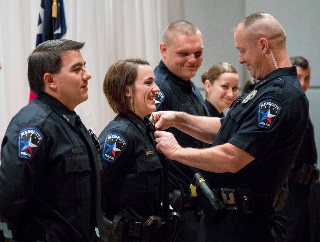 Officer Blythe Moehring of Oceanside, Calif., has her badge pinned by her father, Officer David Moehring, during graduation from the Mesquite police academy at the Mesquite Arts Center on Oct. 5. The Mesquite Police Department graduated 10 officers from the academy.
