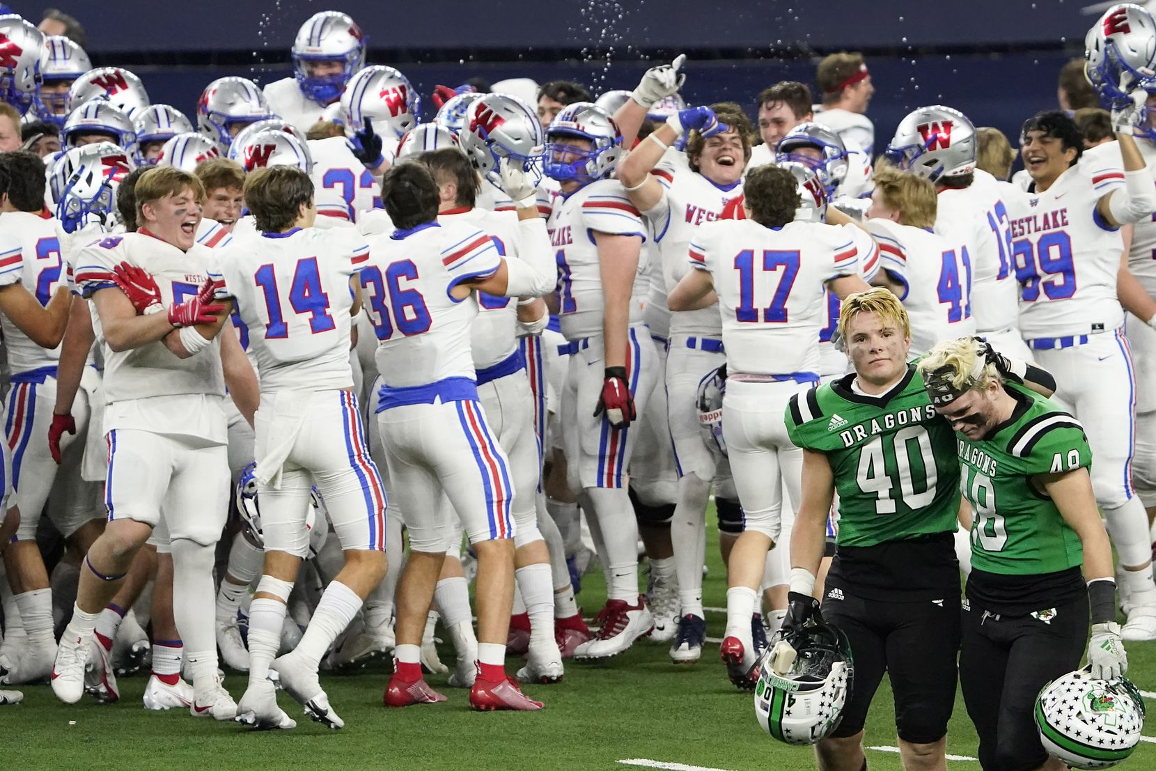 Southlake Carroll linebackers Allan Kleiman (40) and Aiden Peil (48)  leave the field while Austin Westlake players celebrate after a 52-34 Westlake victory in the Class 6A Division I state football championship game at AT&T Stadium on Saturday, Jan. 16, 2021, in Arlington, Texas.