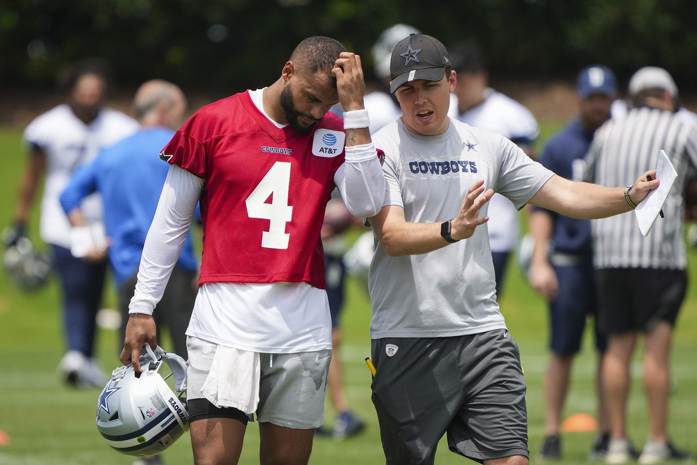 Dallas Cowboys quarterback Dak Prescott (4) scratches his head talks with offensive coordinator Kellen Moore during a minicamp practice at The Star on Tuesday, June 8, 2021, in Frisco. (Smiley N. Pool/The Dallas Morning News)