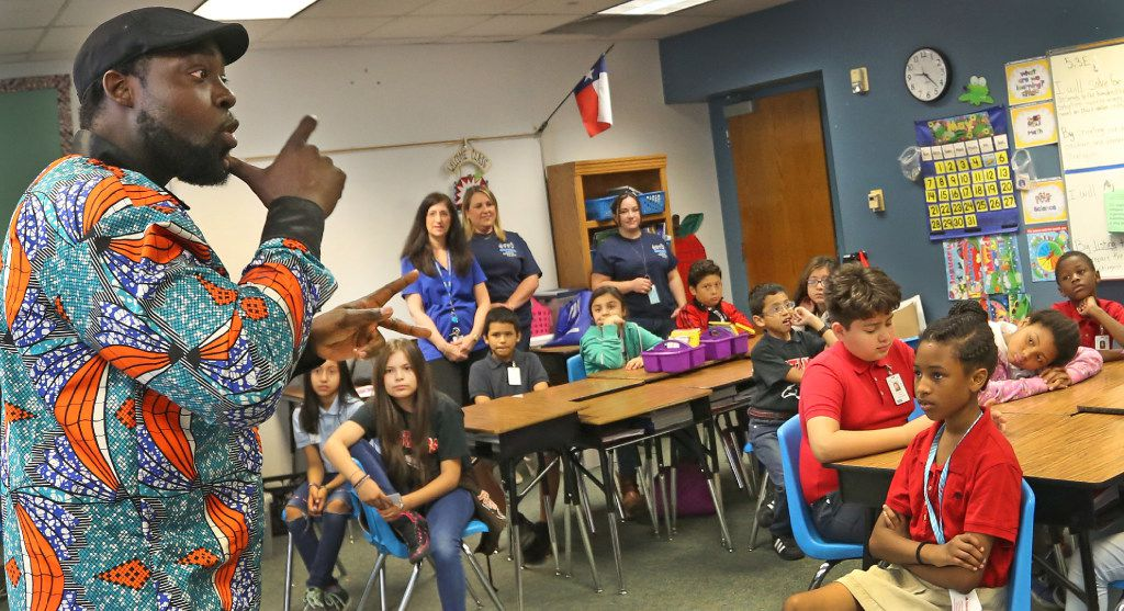 Antoine Dinka, who as a youngster attended Britain Elementary, signs to students as he tells them about his life, as the Irving ISD marks Deaf Awareness Day with a program about deaf education held at Britain Elementary School, 631 Edmonson St. in Irving, TX, on Friday, May 12, 2017. (Louis DeLuca/Dallas Morning News)