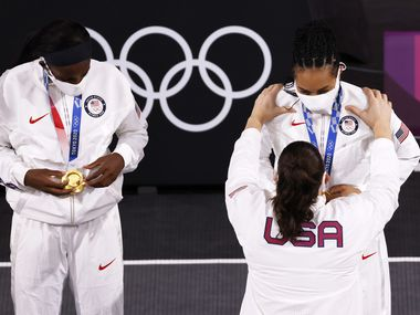USA's Stefanie Dolson (13) puts a gold medal on Allisha Gray (15) as Jacquelyn Young (8) looks at hers during the medal ceremony at the 3x3 women's basketball final at the postponed 2020 Tokyo Olympics at the Tokyo Aomi Urban Sports Park on Wednesday, July 28, 2021, in Tokyo, Japan. USA defeated ROC 18-15 to earn a gold medal. (Vernon Bryant/The Dallas Morning News)