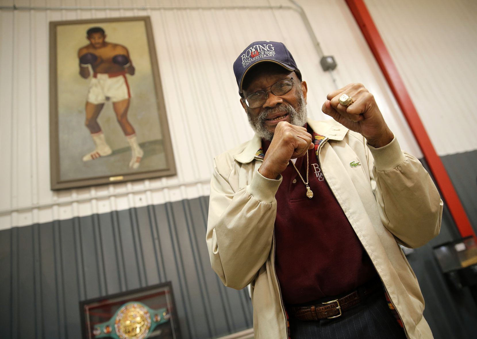 Longtime boxing trainer and former welterweight champion Curtis Cokes poses before a painting of himself at 36 yrs-old before a grand re-opening and ribbon cutting of the multipurpose Behind Every Door Life Center at the Village Oaks Apartments in southern Dallas, Wednesday, January 22, 2014.  The Center provides the surrounding neighborhood with a workout facility and sports leagues, boxing programs, and life skills programs.