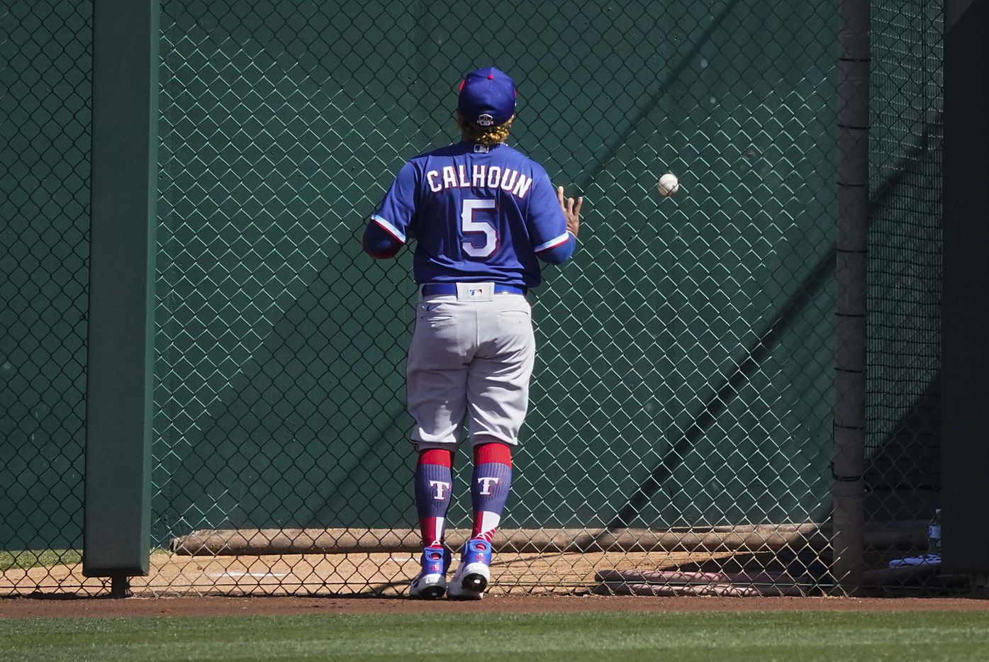 Texas Rangers left fielder Willie Calhoun watches a 3-run home run off the bat of Chicago White Sox designated hitter Andrew Vaughn off of Rangers pitcher Kohei Arihara land in the bullpen during the first inning of a spring training game at Camelback Ranch on Tuesday, March 2, 2021, in Phoenix, Ariz.