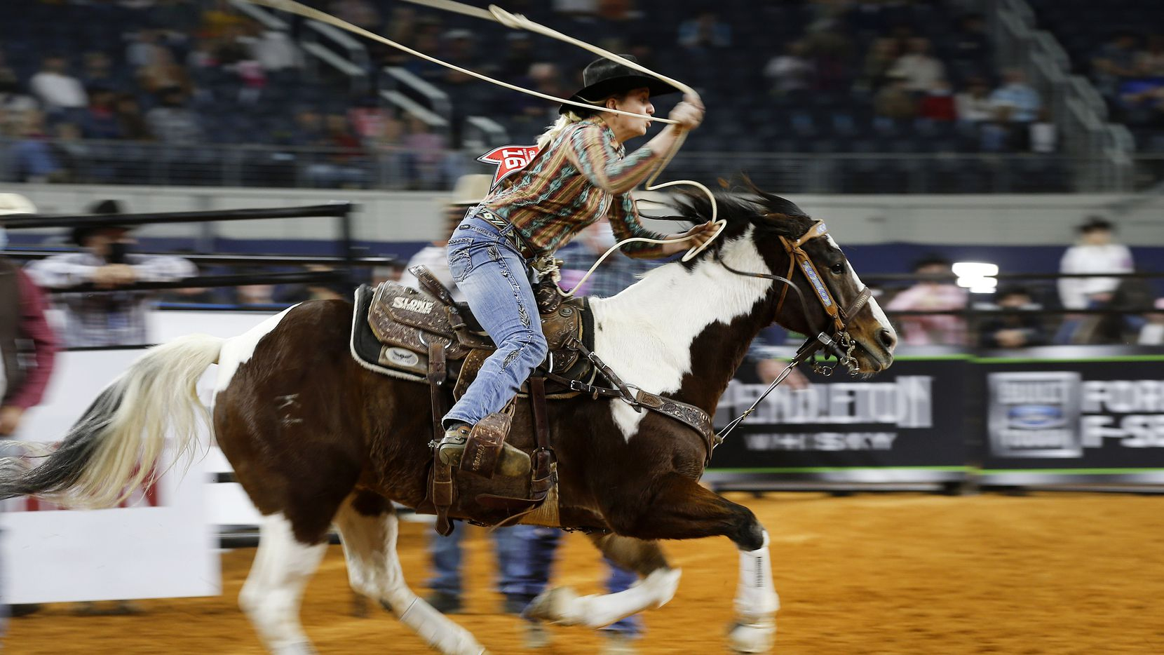 Sawyer Gilbert races from the gate before roping a calf in the breakaway roping final of the inaugural Women's Rodeo World Championship at AT&T Stadium in Arlington, Sunday, November 15, 2020. Less than a month later, the city will host another rodeo event.