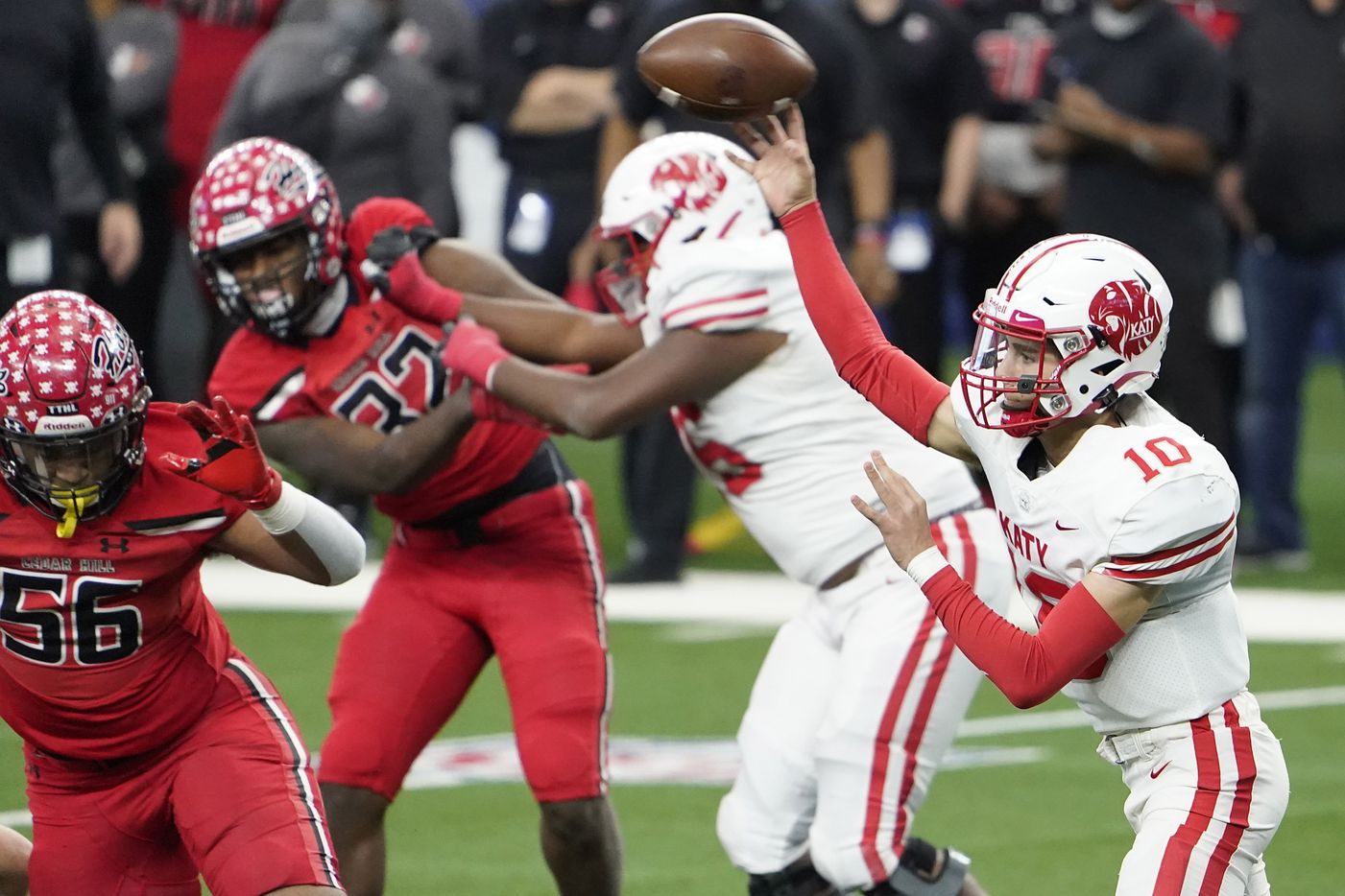 Katy quarterback Caleb Koger (10) throws a pass under pressure from Cedar Hill defensive end Harvey Dyson (56) during the first half of the Class 6A Division II state football championship game at AT&T Stadium on Saturday, Jan. 16, 2021, in Arlington, Texas.