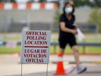 A woman wearing a face mask passes a polling place sign outside a Collin County Early Voting Location at Carpenter Park Recreation Center on Monday, June 29, 2020, in Plano. Monday was the first day for early voting for the July 14 primary runoff election.(Smiley N. Pool/The Dallas Morning News)