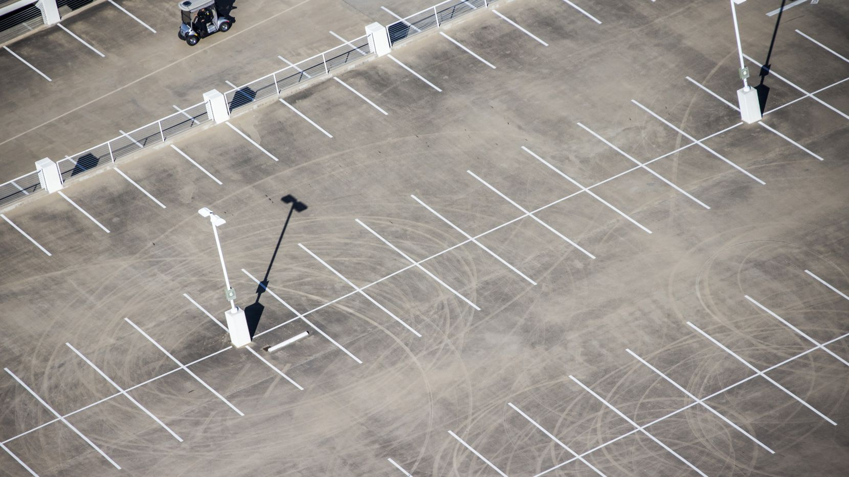 A security guard drives a golf cart past tire marks showing evidence of stunt driving on the top level of a parking garage where two Chinese nationals were struck by a vehicle in March 2019 on the northwest side of NorthPark Center in Dallas.