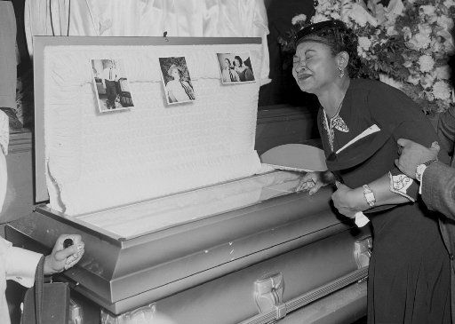 In this 1955 file photo, Mamie Mobley, mother of Emmett Till, pauses at her son's casket at a Chicago funeral home. The 14-year-old Chicagoan was killed in 1955 after reportedly whistling at a white woman during a visit to his uncle's house in Mississippi. Nearly 100,000 people visited his glass-topped casket during a four-day public viewing in Chicago. Images of his battered body helped spark the civil rights movement.