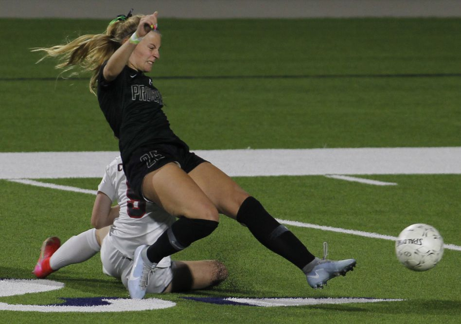 Prosper's Lola Gregory (26) grimaces as she collides with Coppell's Sadie Ozymy (5) yet maintains her balance to pass to a teammate during first half action. Prosper prevailed 2-0 to advance. The two teams played their Class 6A bi-district girls soccer playoff game at McKinney ISD Stadium in McKinney on March 26, 2021. (Steve Hamm/ Special Contributor)