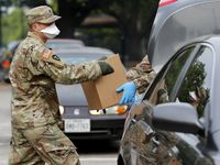 State National Guard soldiers of the 3rd Battalion, 144th Infantry Regiment from Wylie, Texas, place boxes of meals into the trunk of a vehicle as they help distribute food at a North Texas Food Bank mobile pantry distribution location in Irving, Texas, Thursday, April 9, 2020.