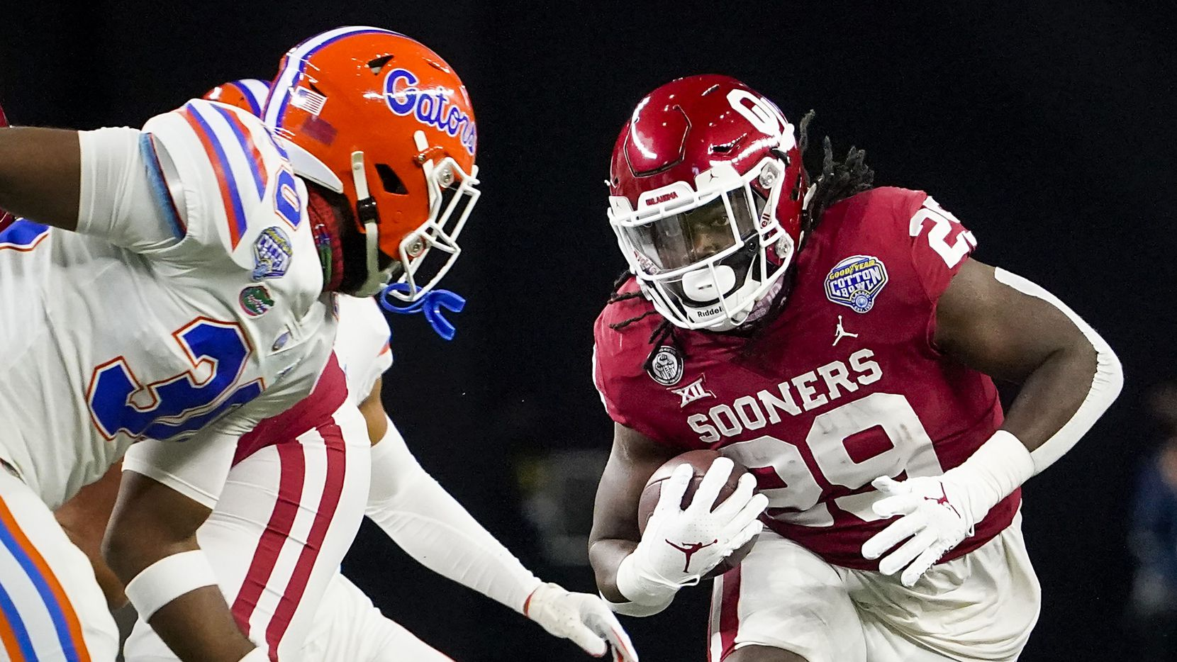 Oklahoma running back Rhamondre Stevenson (29) finds a hole as Florida linebacker Amari Burney (30) closes in during the first half of the Cotton Bowl Classic at AT&T Stadium on Wednesday, Dec. 30, 2020, in Arlington.