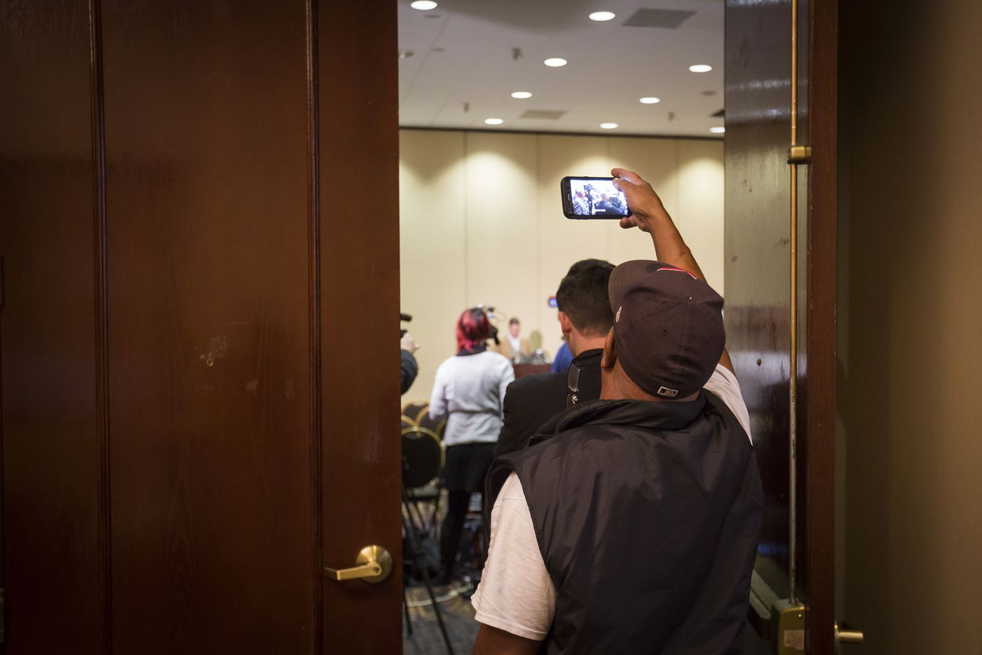 A man passing in the hallway takes a photo through the doorway as Richard Spencer addresses the media.