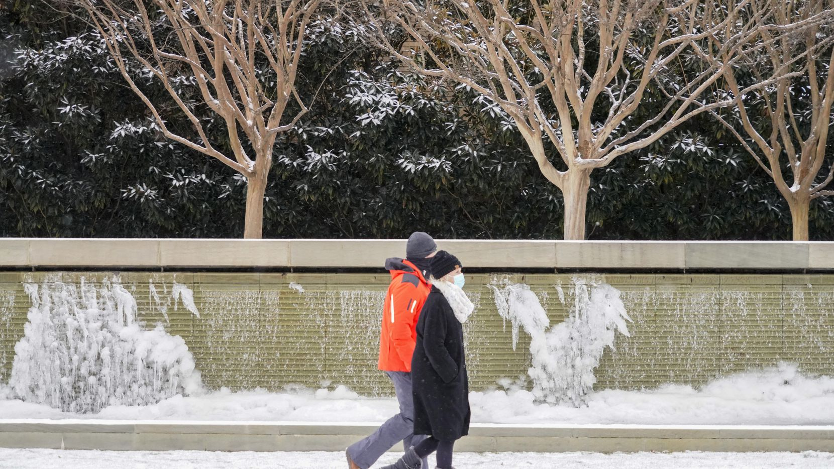 People walk past frozen fountains on Hillcrest near Lovers lane as a winter storm brings snow and freezing temperatures to North Texas on Sunday, Feb. 14, 2021, in University Park.