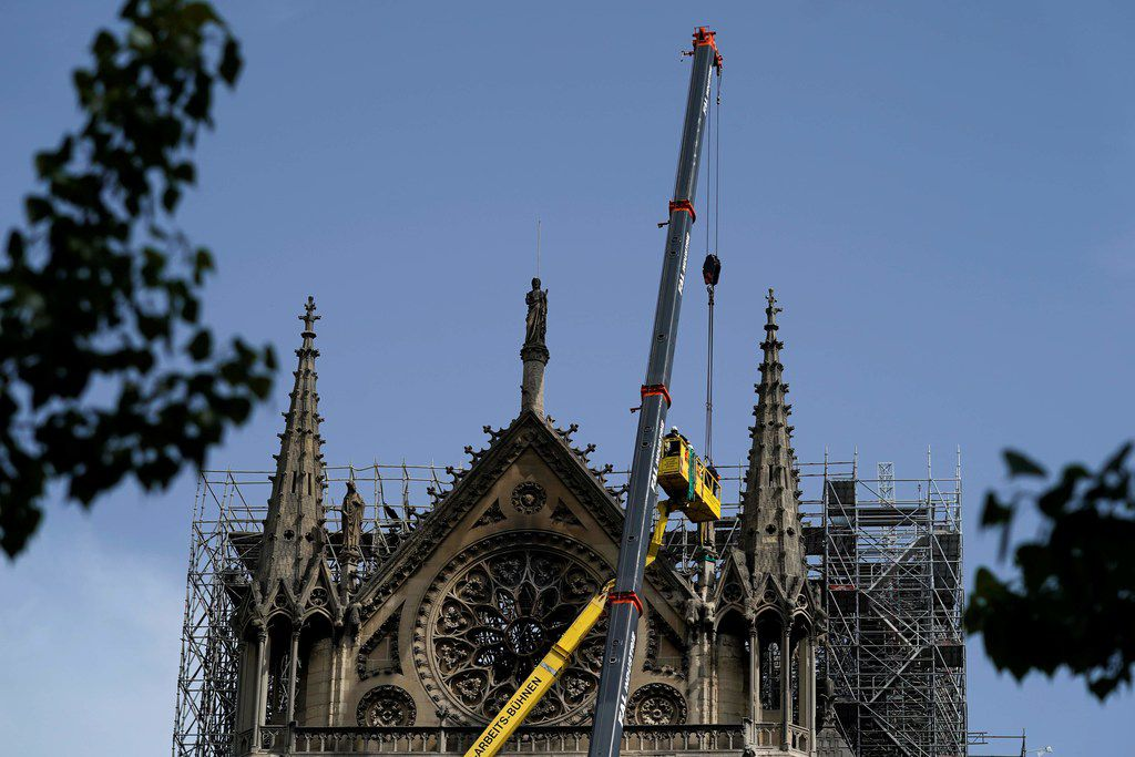 Workers cover and protect the rosette seven days after a fire devastated the cathedral.