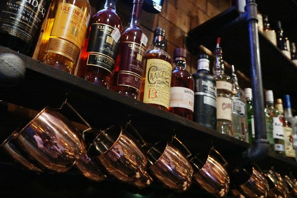 Cool brass cups hang under several bottles of alcohol at Dot's Hop House & Cocktail Courtyard in Dallas, Texas on Tuesday, November 8, 2016. Dot's offers beer, mixed drinks and great food. (Lawrence Jenkins/Special Contributor)