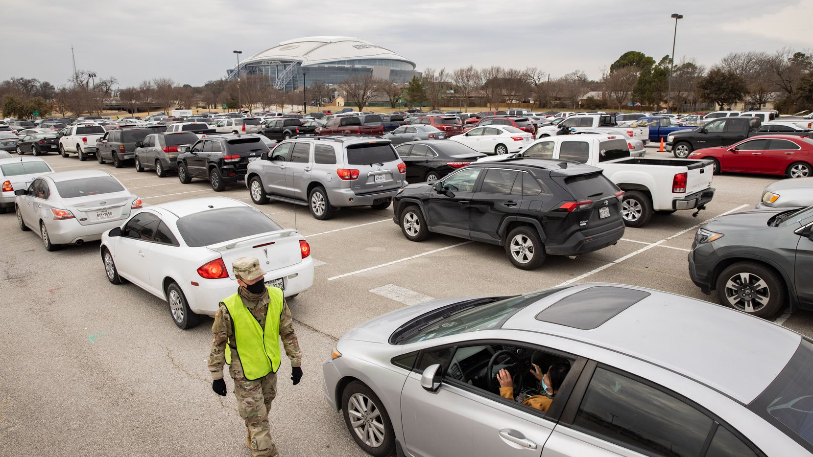 People wait in line to receive food from the Tarrant Area Food Bank in the parking lot of Globe Life Field in Arlington on Thursday, Feb. 25, 2021.