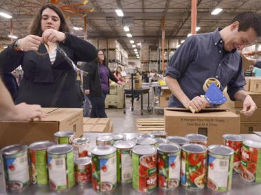 In this file photo, Kevin Moriarty and Rachel Hull with the Dallas Theater Center volunteer at the North Texas Food Bank in Dallas.