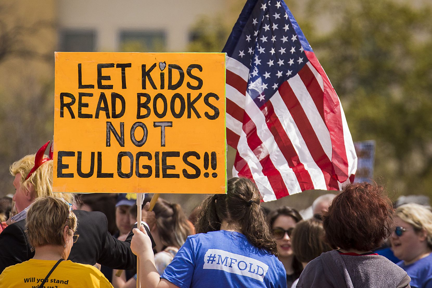 """A sign reads """"Let kids read books not eulogies!!"""" in reference to recent school shootings."""
