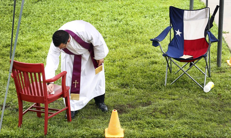 The Rev. Michael Picard, a Regnum Christi priest, disinfected a parishioner's chair after a confession at The Highlands School in Irving. Priests took confessions from parishioners under tents as they drove up in their cars Sunday, March 22, 2020. With public spaces shut down amid the coronavirus pandemic, churches are getting creative about providing sacramental relief to their members.(Tom Fox/The Dallas Morning News)