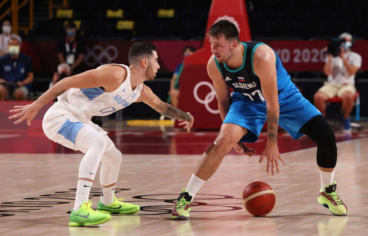 Slovenia's Luka Doncic (77) dribbles between his legs as he is defended by Argentina's Luca Vildoza (17) in the first half of play during the postponed 2020 Tokyo Olympics at Saitama Super Arena on Monday, July 26, 2021, in Saitama, Japan. Slovenia defeated Argentina 118-100. (Vernon Bryant/The Dallas Morning News)