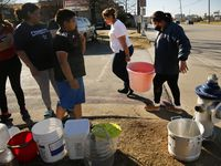 """For those of you still hurting, I want you to know that the state is using every resource to fix this problem,"" Gov. Greg Abbott said of Texans' suffering from power and water outages as a result of last week's bitter cold weather. In photo, residents of Villas Del Solamar Apartments who'd been without water for a week waited to fill buckets Monday at a fire hydrant on Park Lane in Dallas."