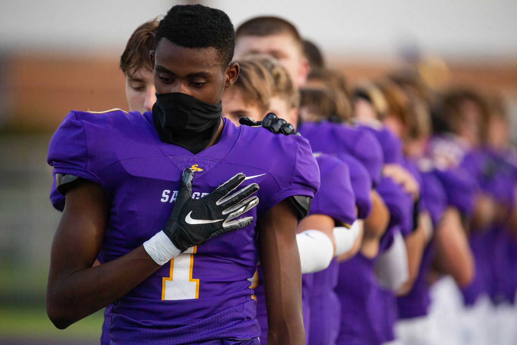 Sanger High School player Josh Henry wears a neck gaiter  during the national anthem before the start of a game against Lake Worth High School on Sept. 4, 2020 in Sanger. Sanger leads 26-14 at halftime. (Juan Figueroa/ The Dallas Morning News)