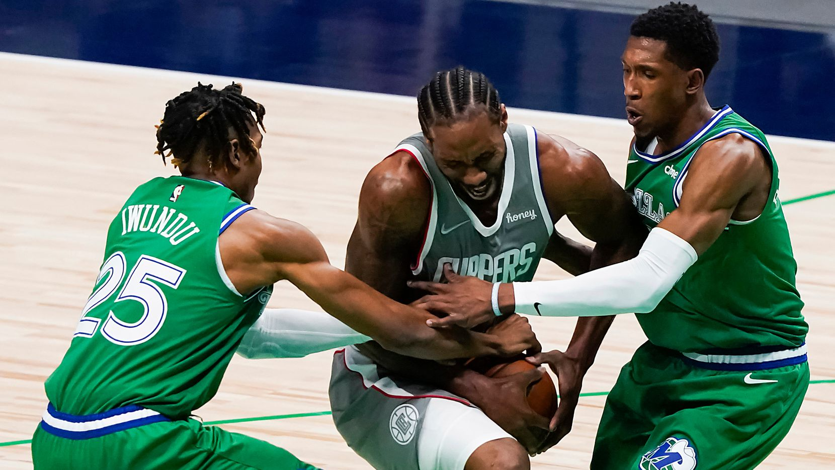 LA Clippers forward Kawhi Leonard (2) is wrapped up by Dallas Mavericks guard Josh Richardson (0) and forward Wes Iwundu (25) during the first quarter of an NBA basketball game at American Airlines Center on Wednesday, March 17, 2021, in Dallas.